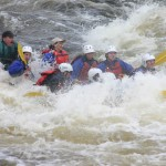 Waves crashing over the top of the whitewater raft